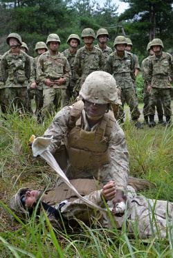 負傷者の救護訓練をする米海兵隊員(手前)を見る陸上自衛隊員(7日、滋賀県高島市の饗庭野演習場)