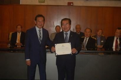 野村サンパウロ市議から表彰状を受け取る与儀会長
