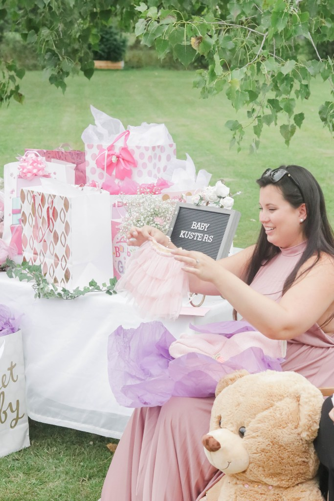 Nikki opening gifts and showing friends and family the adorable baby tutu gifted to Baby Kusters!