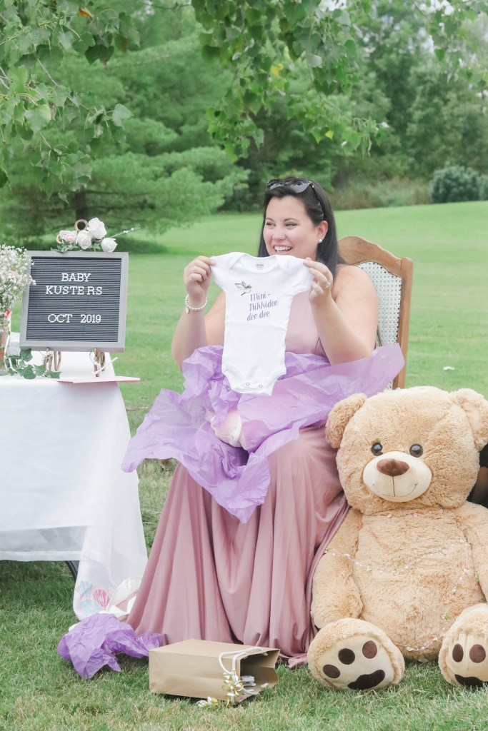 Nikki showing off a cute baby onesie at her pretty in pink baby shower.