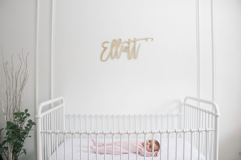 Elliott's White Vintage Crib; White walls, cursive name sign on wall, wainscotting, bright white baby girl room. #babygirlnursery    Nikki's Plate