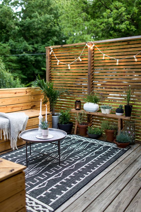 15 Deck Must Haves for Summer Entertaining; potted plants, privacy wall, outdoor hanging lights on deck