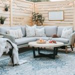 15 Deck Must Haves for Summer Entertaining; comfy sectional, comfy seating coffee table, blue outdoor rug, privacy wall with lights