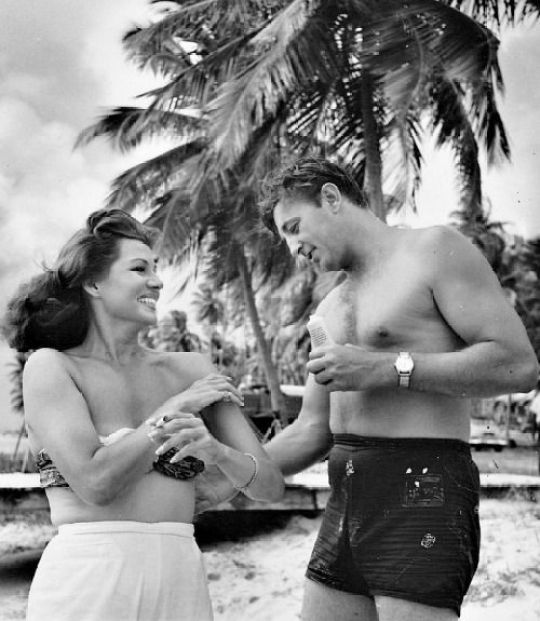 Ο Robert Mitchum βάζει αντιηλιακό στην Rita Hayworth