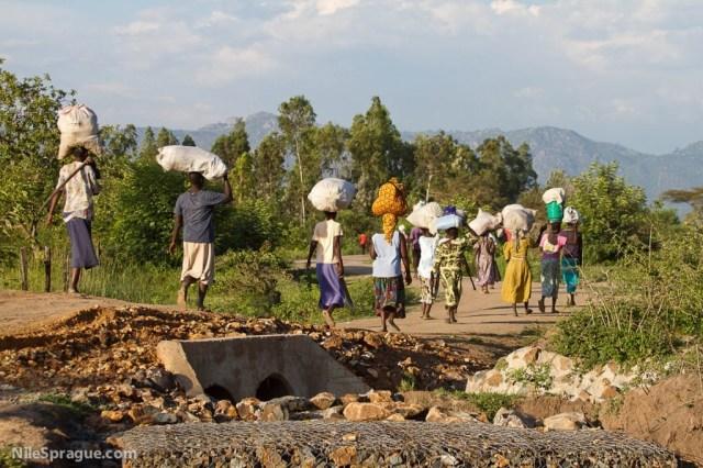 Women carrying sacks on their heads after market, Kisumu, Kenya.