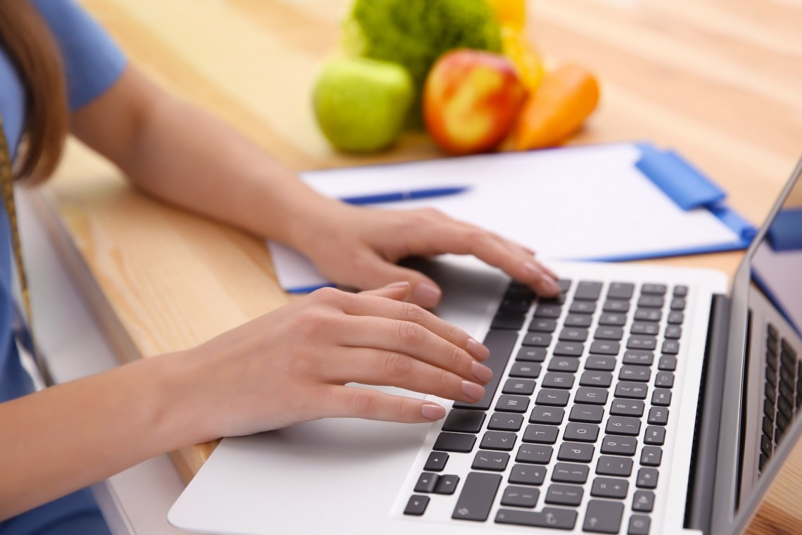Young female nutritionist working with laptop in office, closeup