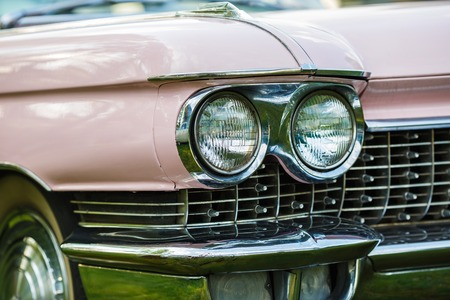 57592917 - detail on the headlight of pink vintage car. selective focus.