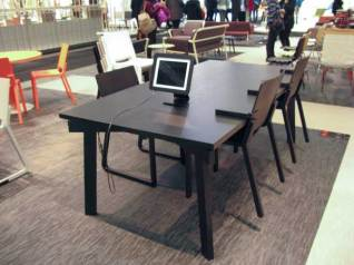 Table with chairs hung on the edge of it. Stand for iPad.