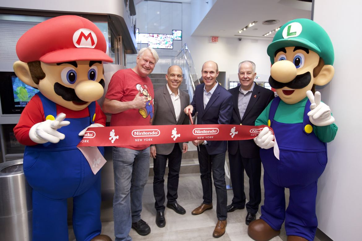 In this photo provided by Nintendo of America, Mario and Luigi unveil the remodeled Nintendo NY store during a ribbon-cutting ceremony on 19th February 2016. Joining the Super Mario Bros. (left to right) are Charles Martinet, the voice of Mario, and Nintendo of America executives Doug Bowser, Vice President of Sales; Scott Moffitt, Executive Vice President of Sales & Marketing; and Rick Lessley, Vice President of the Supply Chain Group.​