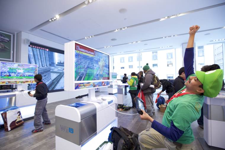 In this photo provided by Nintendo of America, Rinaldy G. of New York plays Mario Kart 8 using the Nintendo NY store's upgraded Wii U demo units at the store's reopening on 19th February 2016.