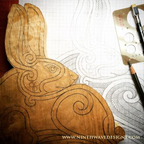 The cut-out of the carving next to the finished design drawing.