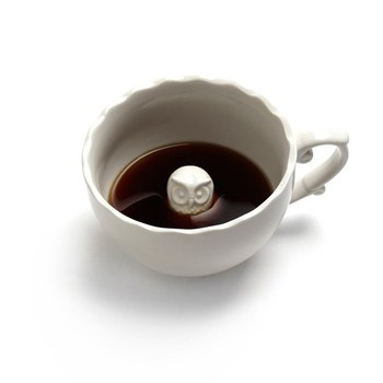Coffee mug with a cute porcelain owl at the bottom