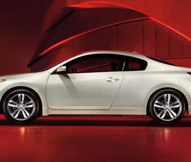 Nissan Altima Coupe Drivers Side Profile In White Set Against A Red Background