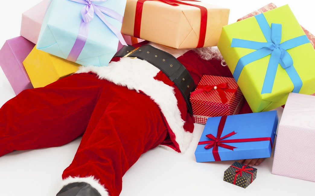 Santa claus too tired to lie on floor with many gift boxes over white background. Foto: iStockphoto