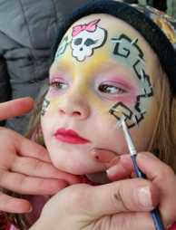 Children receiving face painting at a party.
