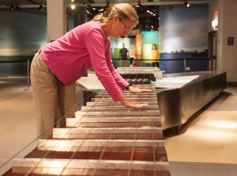 A woman plucks the strings of the world's largest guitar, at Liberty Science Center.
