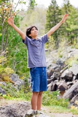 Teenage boy raising hands in praise
