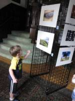 A young visitor enjoys the Three Generations Photography Exhibit at the Pen Arts Building