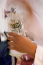 Photograph of a nurse placing an IV bag on a pole