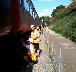 Nationwide Building Society volunteers, Rob, Vicky, Helen and Paul paint the B4 bogies of 5174 with black chlorinated rubber paint. Photo: D.Millard
