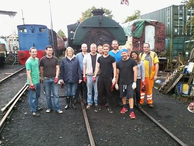 Nationwide Building Society volunteers stand in front of the Peckett steam locomotive, with Facilitator David Millard in orange Hi-Viz. Photo: G.Titmuss