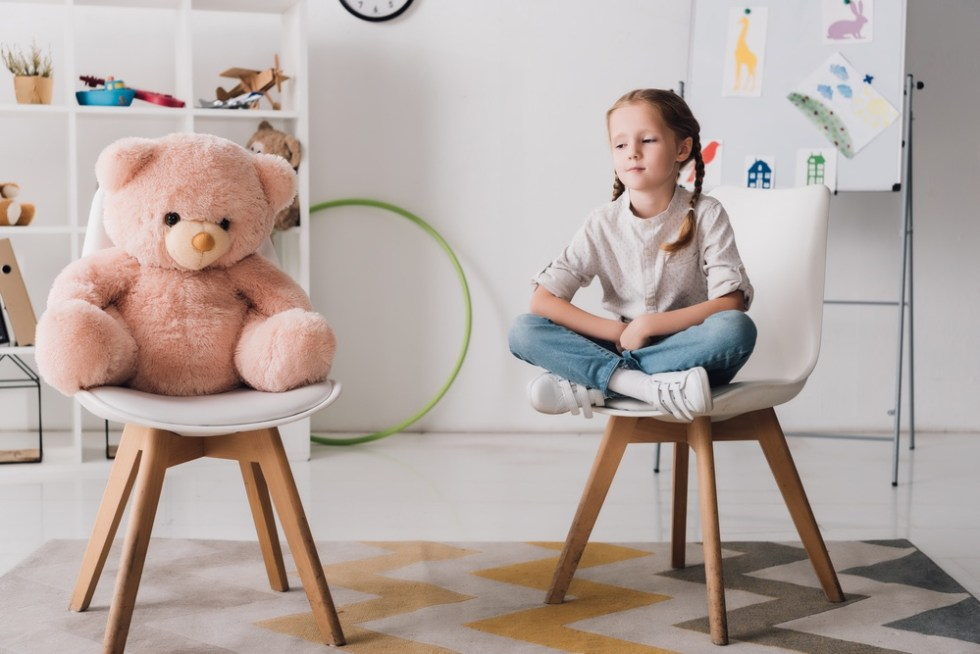 Lonely little girl with teddy bear.
