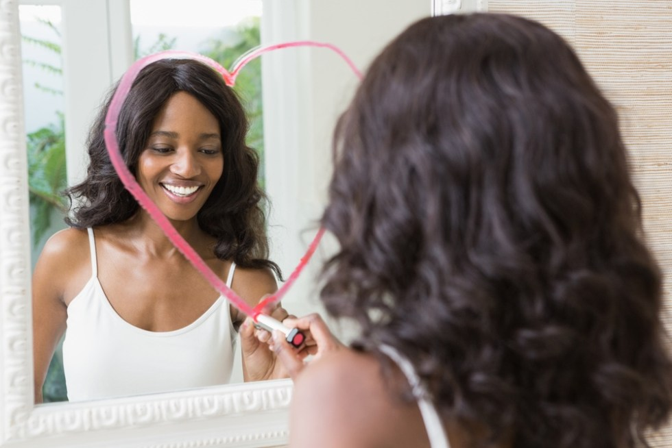 Woman drawing heart and looking at her reflection in the mirror
