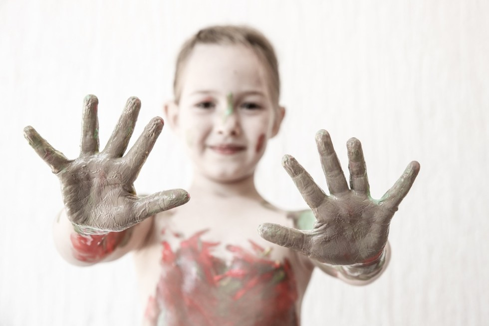 Happy girl with paint on her hands. Messy play.