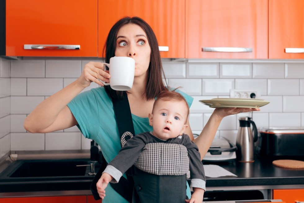 Overwhelmed multitasking mom with dishes, cup of coffee and baby