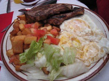 """El Jefe"" - two grilled pork chops, two eggs (any style) and fried potatoes."