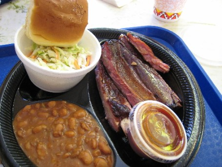 An order of ribs and two sides: coleslaw and spicy beans.