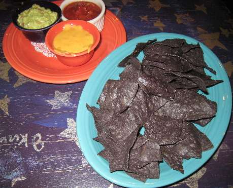 A trio of salsa, con queso and guacamole with blue corn tortilla chips