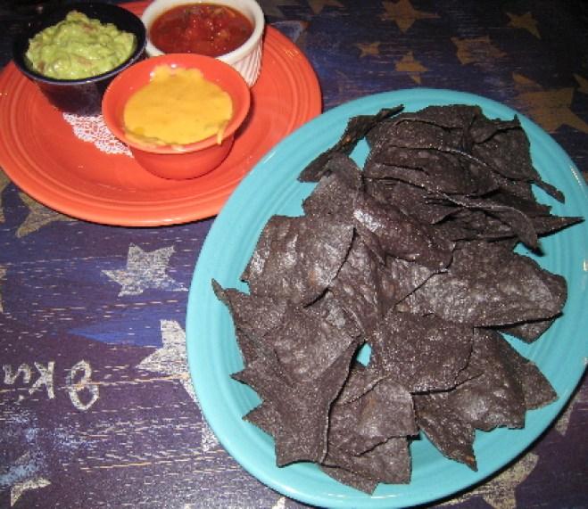 A trio of salsa, con queso and guacamole with blue corn tortilla chips