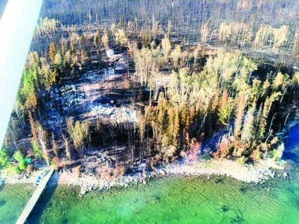 Above are the charred remnants of Namushka Lodge the day after a wildfire raged through last summer. There were 21 guests at the lodge at the time who fled by boat. photo courtesy of Bryan Chorostkowski