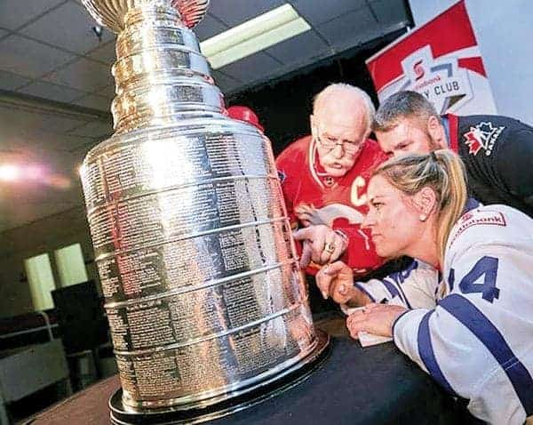 NHL Hall of Famer Lanny McDonald, left, and Natalie Spooner of the Canadian Women's Hockey League's Toronto Furies inspect the Stanley Cup during the trophy's stop in Iqaluit on April 26. It was the first of eight stops over four days for hockey's biggest prize through the territory. - photo courtesy of Project North
