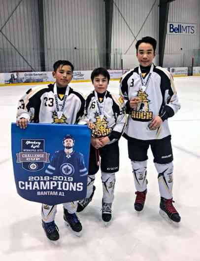 Rankin Rock bantam players, from left, Koby Connelly, Kadin Eetuk and Chase Harron celebrate with the championship banner after claiming the A1 Division at the Winnipeg Jets Challenge Cup tournament in Winnipeg, Man., on Dec. 30, 2018. Photo courtesy James Connelly