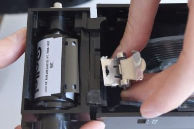 I preparativi per l'aggancio della pellicola: la pinza deve perforare la pellicola esattamente al centro; in basso a sinistra la pellicola agganciata, a questo punto la tank va chiusa con il suo coperchio.