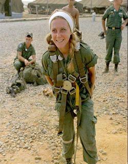 """Photo courtesy: ©Bob Cole 22 Febbraio 1967. Catherine Leroy, di anni 21, nei mo- menti antecedenti al lancio col paracadute per l'opera- zione """"Junction City"""". Sopra al paracadute d'emergen- za, Nikon e Leica: le sue """"armi"""" preferite."""