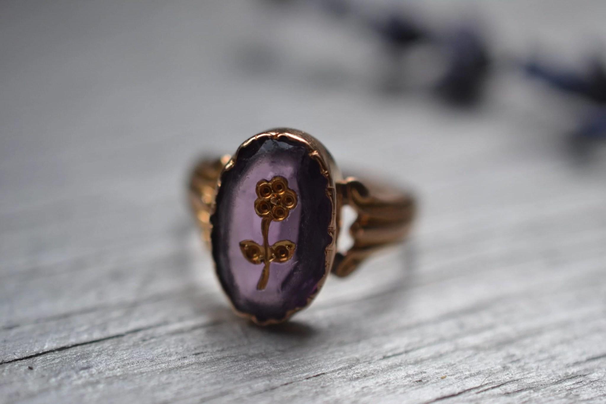 Bague vintage en or jaune 18 carats (750/1000), sertie d'une pierre couleur violet et gravée d'une fleur - un bijou Noircarat.fr