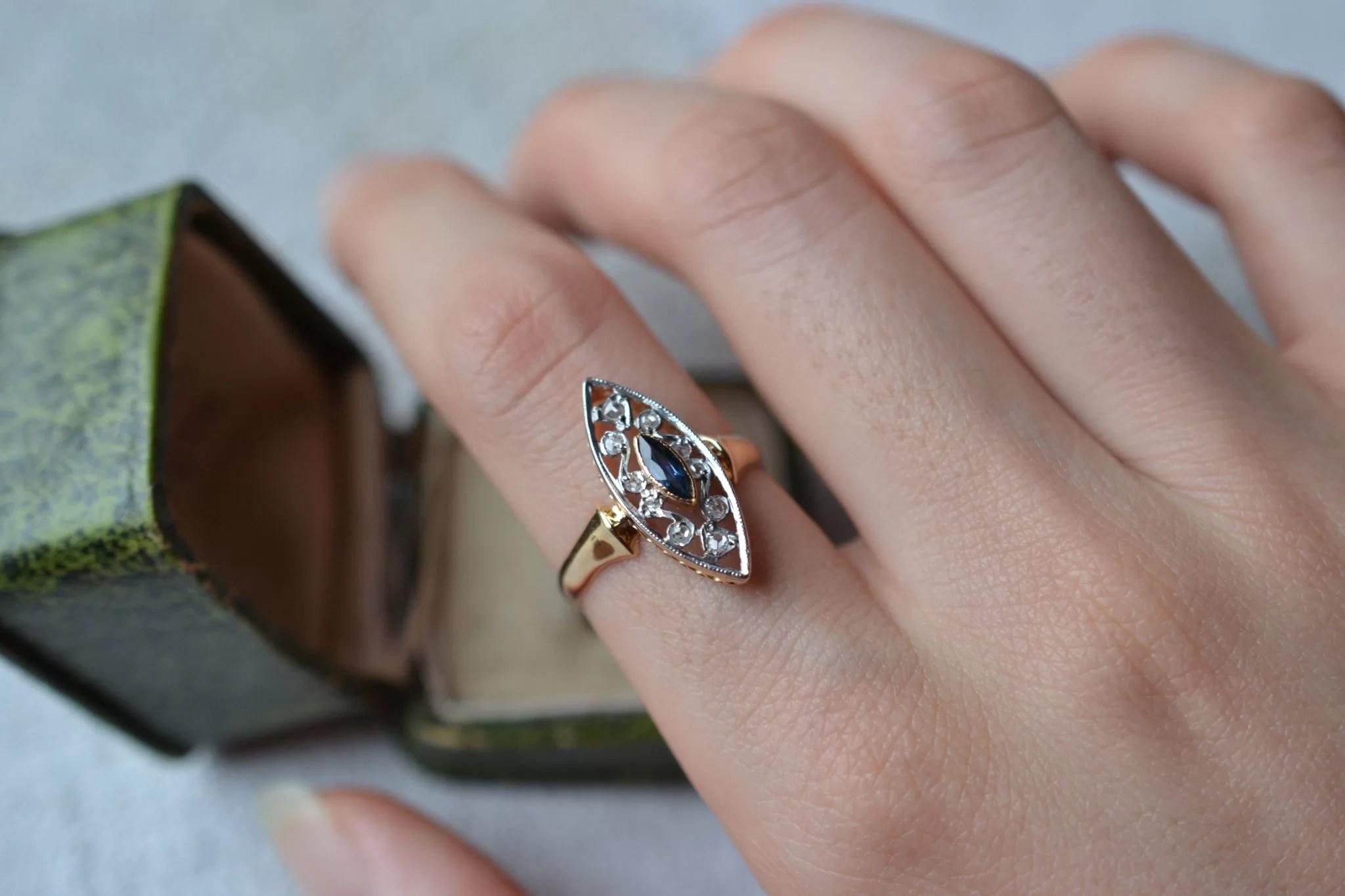 Bague en Or jaune et Or blanc, de forme Marquise, sertie d_un saphir de taille navette facettée et ponctuée de diamants de taille rose - bague rétro