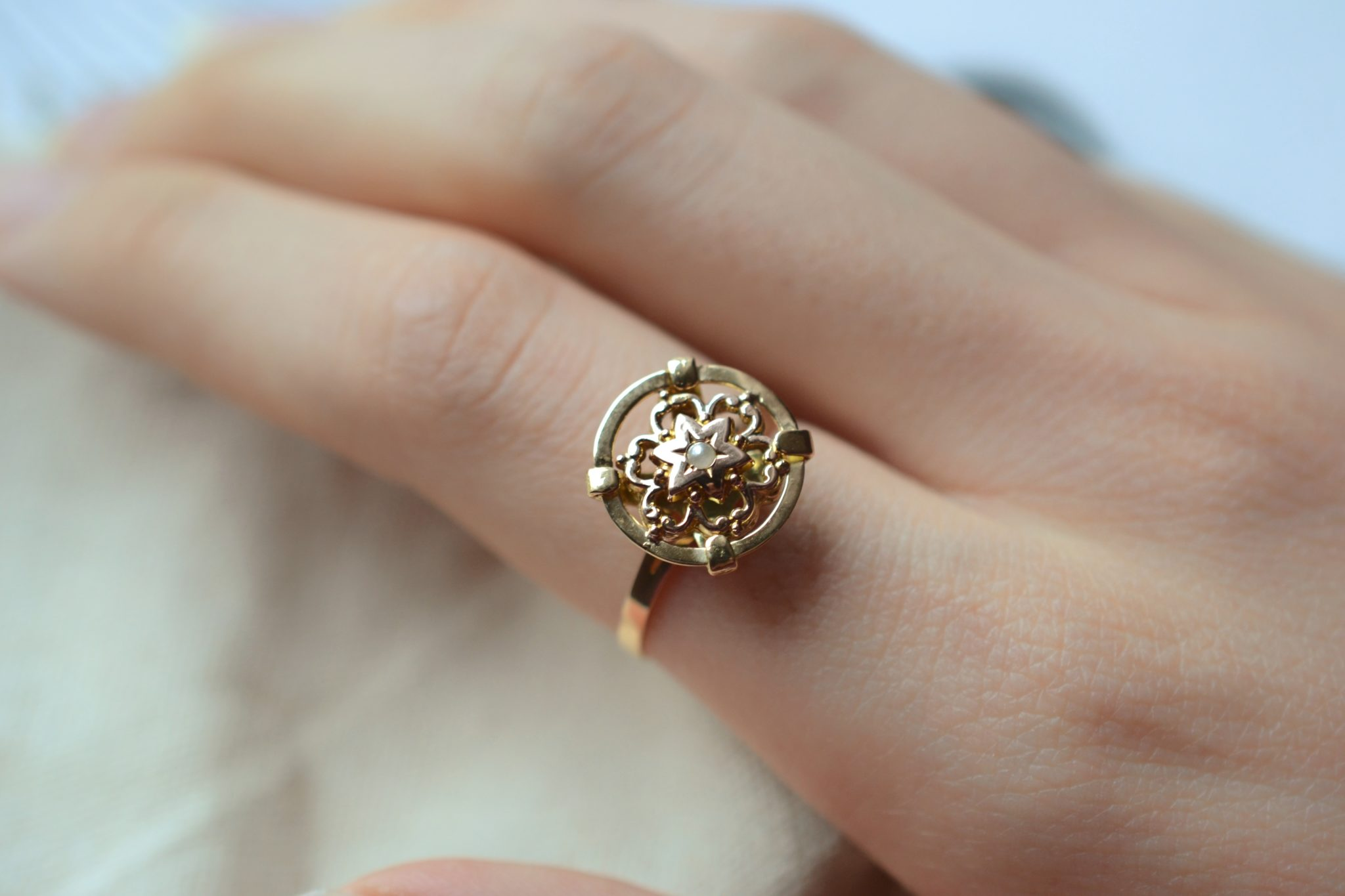 Bague en Or jaune ornée d_une demi-perle de culture sur un plateau en forme de disque, décoré d_un motif fleuri en Or rose - bague ancienne