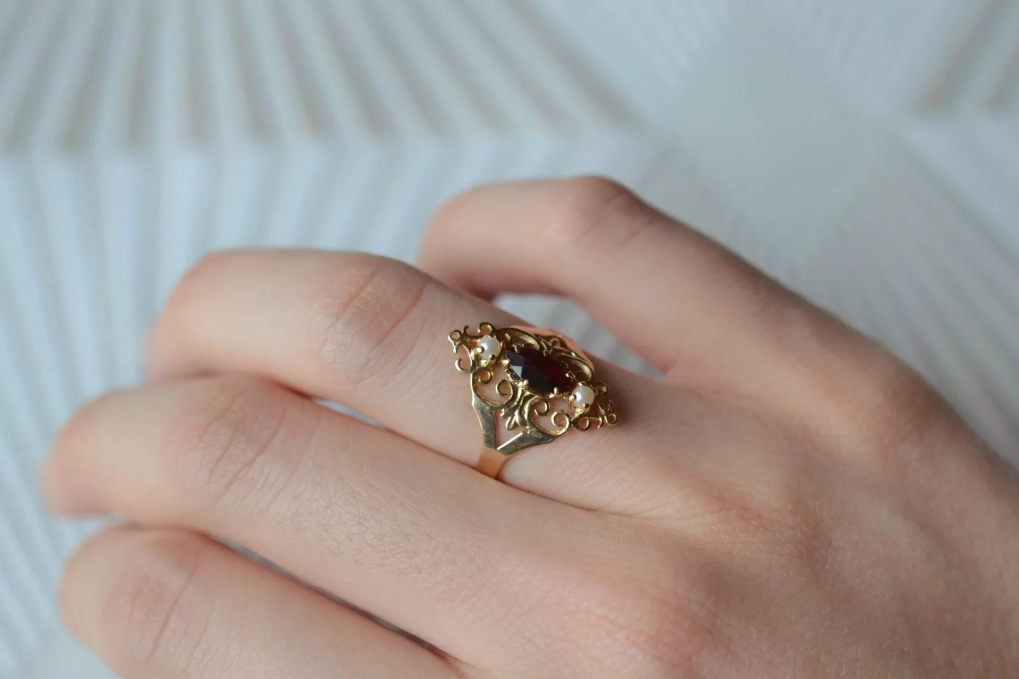 Bague en Or jaune ornée d_une pierre bordeaux accompagnée de deux perles - bague rétro