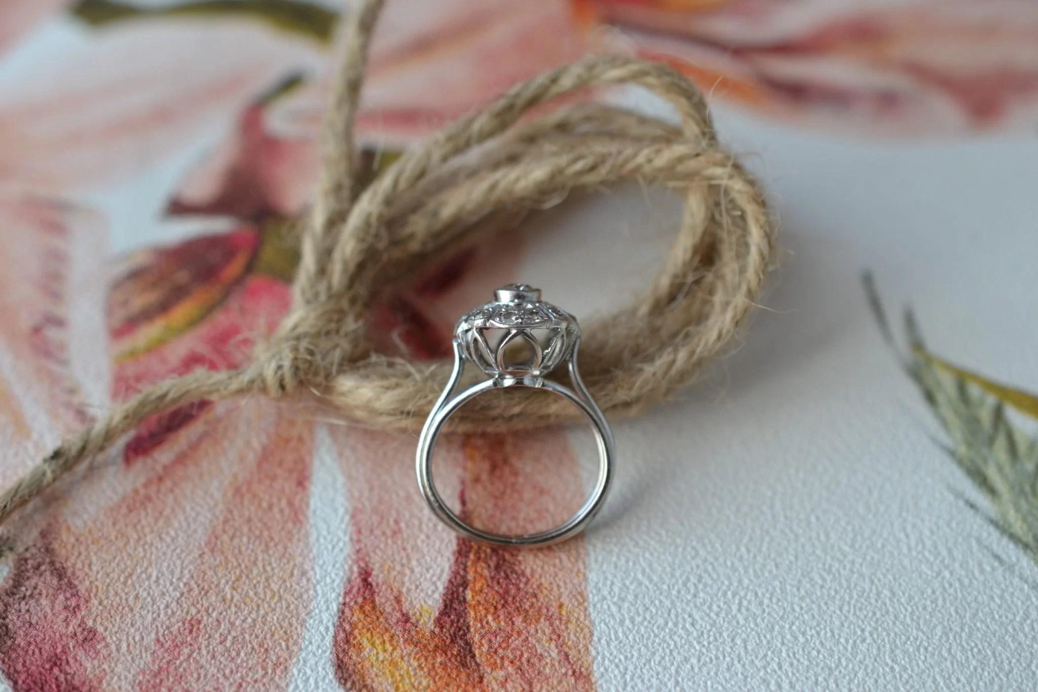 Bague solitaire en Or blanc sertie d_un diamant dans un entourage de brillants - bague rétro