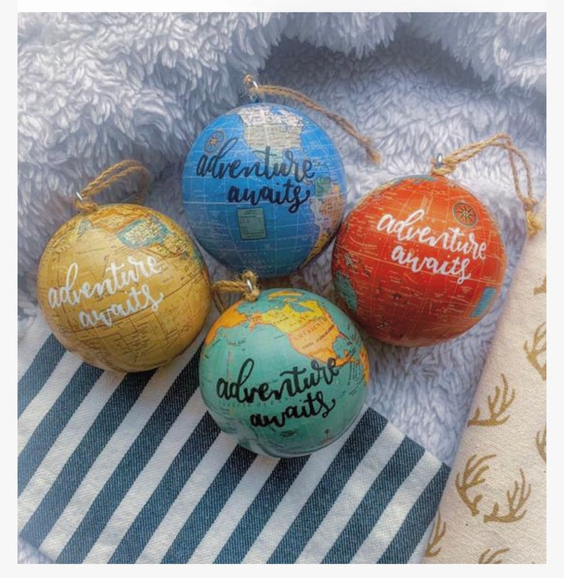 "Multi-colored globe ornaments with text reading ""Adventure awaits"""