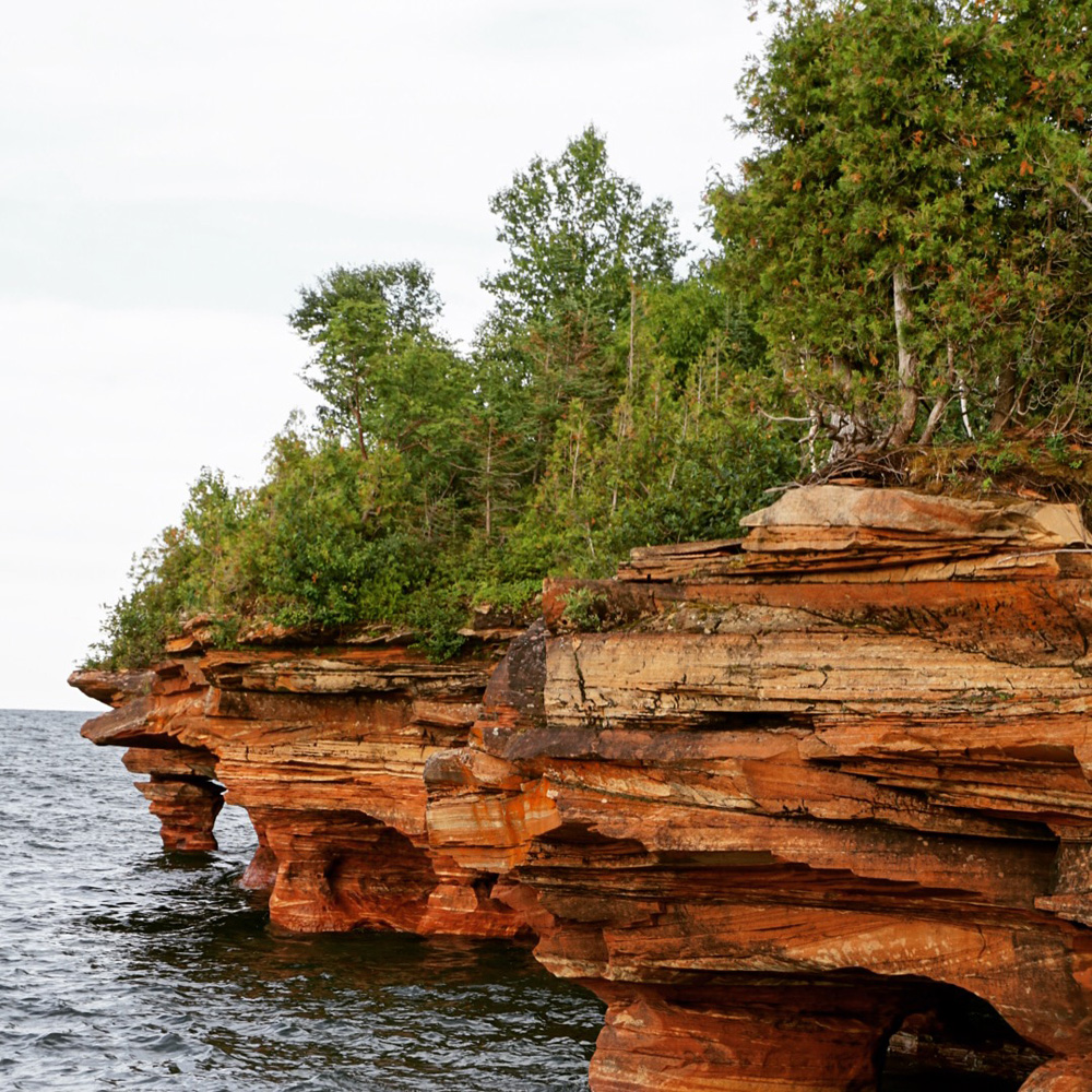Reddish cliffs along a lakeshore