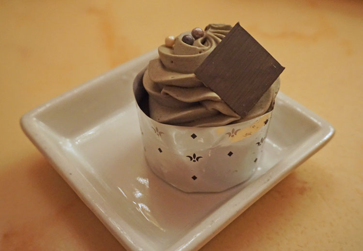 "Cupcake with chocolate embellishment and ""grey stuff"" frosting at Disney's Be Our Guest restaurant in the Magic Kingdom"