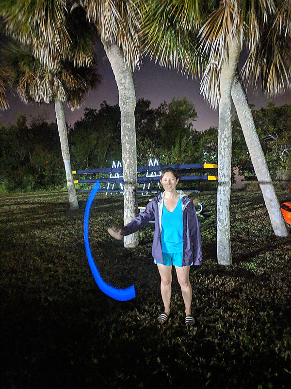Woman twirling glow stick before a bioluminescence kayaking tour in Florida