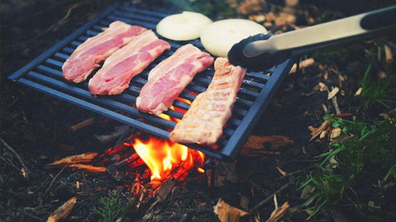 Food cooking on a roll-up grill from a list of the best camping gifts.