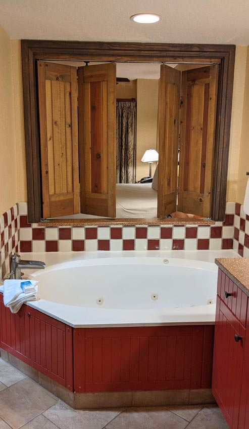 Jacuzzi tub with shutters open toward a bedroom at the Wilderness Lodge DVC villas