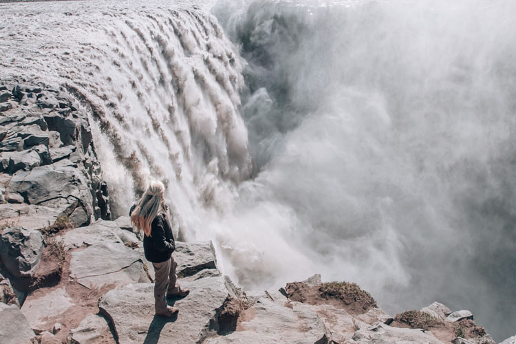 Woman standing near the brink of Dettifoss in Iceland